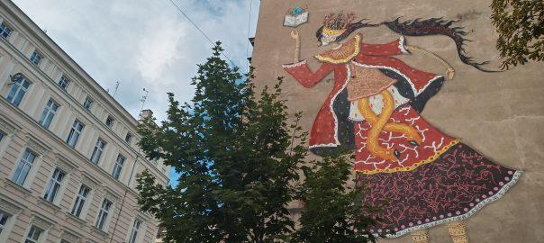 Mural przedstawiający kobietę czytającą książkę. Na pierwszym planie korona drzewa, w tle inne kamienice
